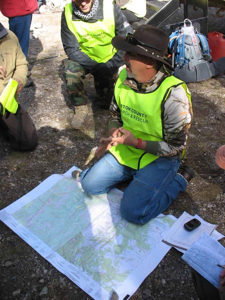 Man kneeling on the ground over a map, talking to others around him