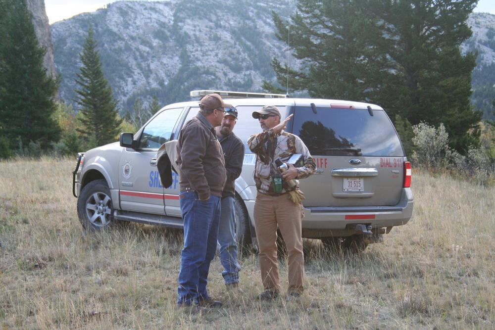 3 men talking by a sheriff's vehicle, one using his arm to indicate the angle of a slope