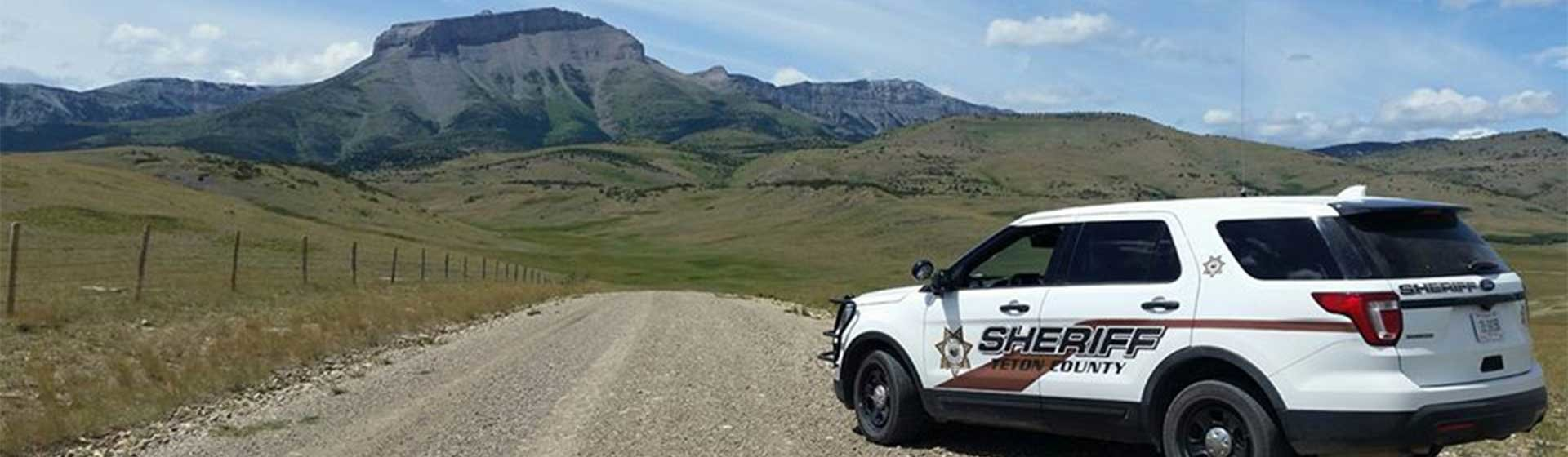 Sheriff vehicle with mountain range in the distance