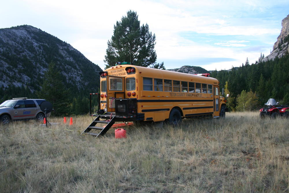 school bus parked in a grassy field with stairs coming out of the back door, sheriff's office vehicle parked next to it